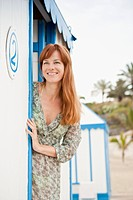 Smiling woman standing near beach hut