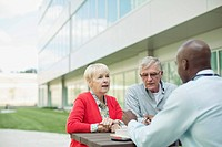 Senior couple consulting with doctor at outdoor table