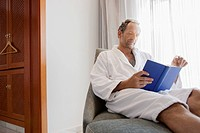 Man in bathrobe reading book