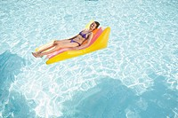 Woman floating on pool raft