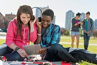 Friends listening to music together at outdoor park.