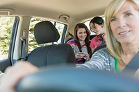Mother driving with teenage girls in the backseat