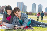 Teenage couple sharing pc tablet at outdoor park