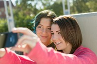 Teenage girls taking portrait using smart phone