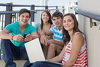 Teenagers sitting on outdoor steps with laptop