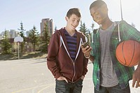 Teenage boys with basketball looking at smart phone