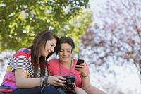 Teenage girls in park with smart phone and camera