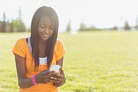 Pretty, African American teenager texting on smart phone