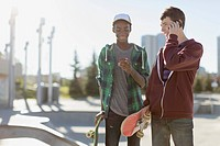 Skateboarders using smart phones in skate_park