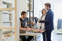 Young adult couple paying for purchase at men's wear store (thumbnail)