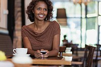 Pretty young adult woman with smart phone in cafe