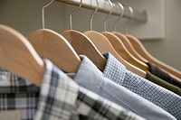 Close_up of men's shirts on wooden hangers