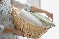 Mid_adult woman carrying wicker laundry basket