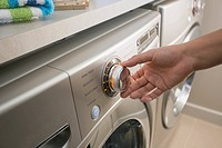 Close_up of woman's hand adjusting dial on washing machine