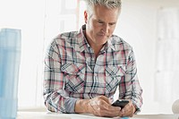 Middle_aged businessman texting on cell phone in office