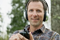 Portrait of mid_adult man with headphones in the park.