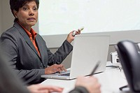 Mature businesswoman using projector at meeting.