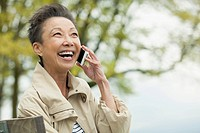 Middle_aged Asian woman having a laugh while on cell phone.