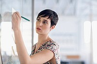 Stylish young businesswoman writing on whiteboard