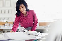 Middle_aged businesswoman reviewing paperwork.