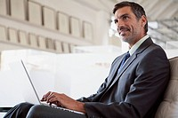 Middle_aged businessman with laptop at office.