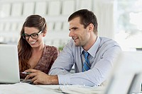 Two businesspeople reviewing information on laptop together