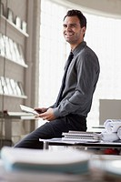 Young architect smiling while sitting on desk