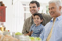 Young boy with his dad and grandpa at dinner table