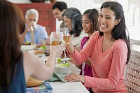 Mid_adult woman toasting with wine at family dinner