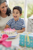 Excited young boy with birthday cake
