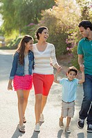 Young Hispanic family smiling while out walking