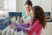 Young girl helping mom with dishes