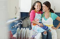 Mother with arm around young daughter in kitchen