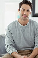 Portrait of handsome Hispanic man sitting at home