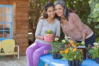 Mother and preteen daughter with flowers to plant