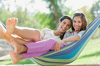 Portrait of preteen sister and older sister in hammock