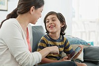 Mother and young son looking at each other while playing with pc tablet