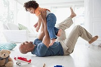 Father lying on the floor and lifting toddler son