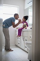 Father helping young daughter brush her teeth