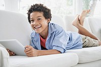 Preteen boy on sofa with pc tablet (thumbnail)