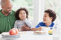 Father having a laugh with sons during breakfast.