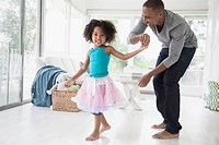 Father twirling young daughter in sunroom