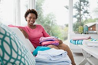 Portrait of mid_adult woman with folded laundry