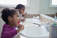 Young sisters brushing their teeth together