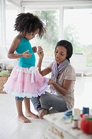 Mother repairing young daugther's dance skirt
