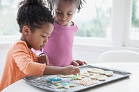 Young sisters decorating cookies together