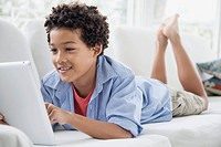 Preteen boy playing with pc tablet on couch