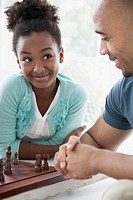 Preteen daughter giving her dad a funny look while playing chess