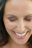 Middle_aged woman laughing with eyes closed