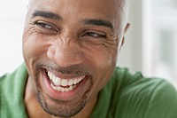 Close_up of African American man laughing.